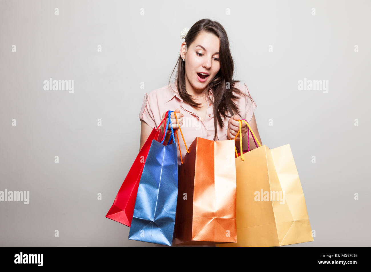 Attractive young woman is very surprised how much she bought on black friday for christmas - Stock Image