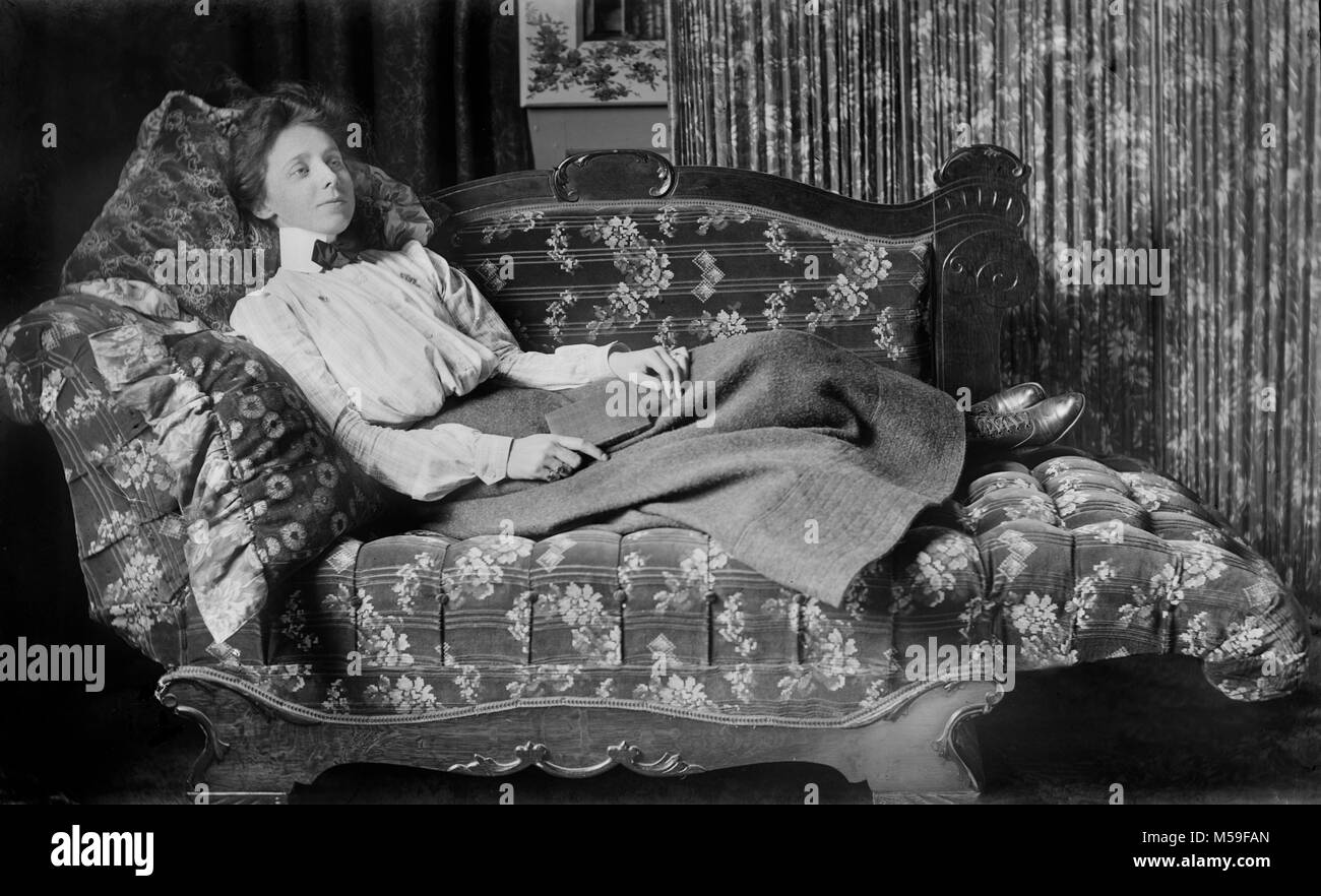 A young Victorian woman takes a break from reading her poetry while lounging on a fainting couch, ca. 1900. - Stock Image