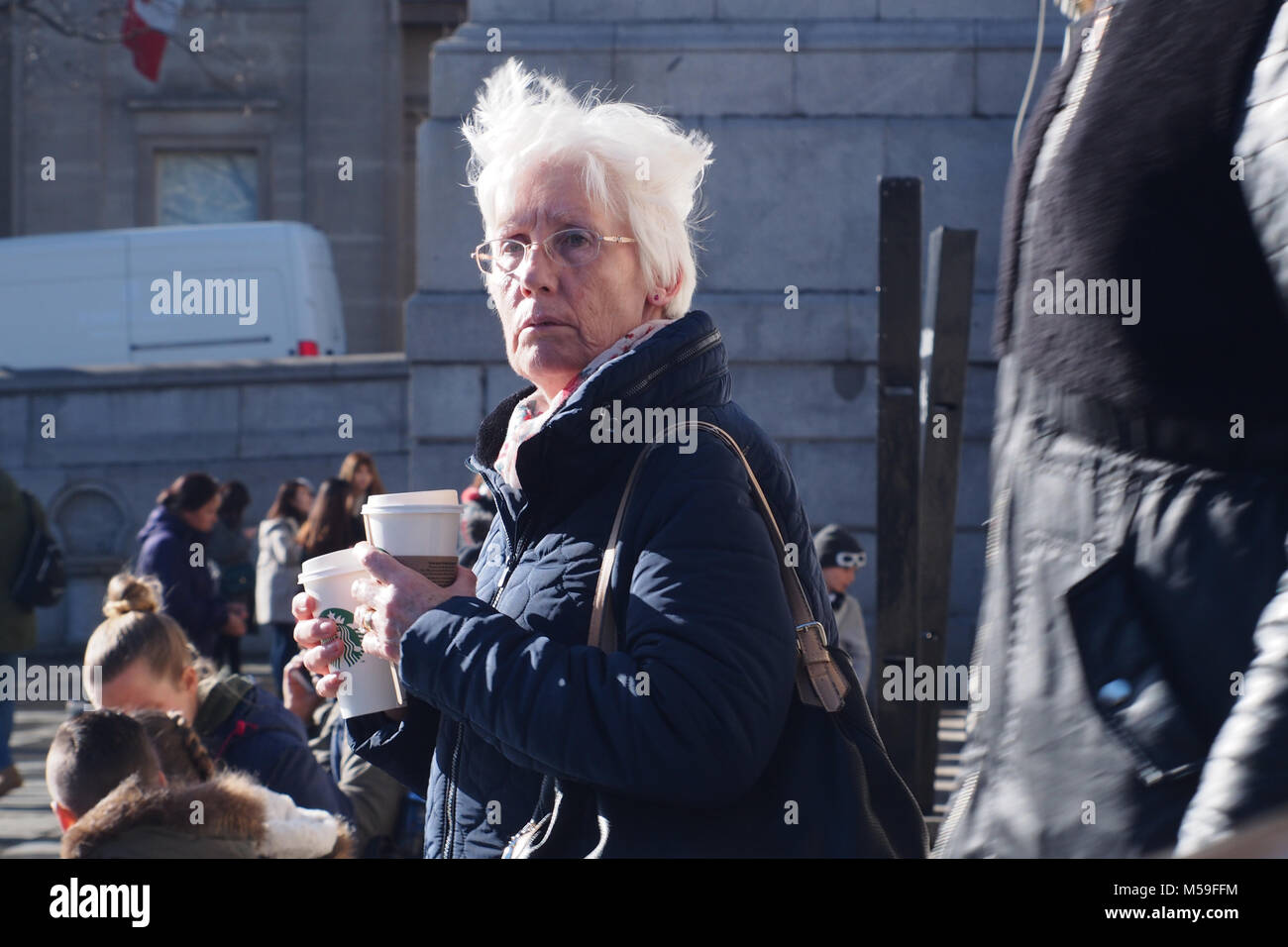 An older woman holding two disposable cups containing hot drinks with people in the background, Trafalger Square, - Stock Image