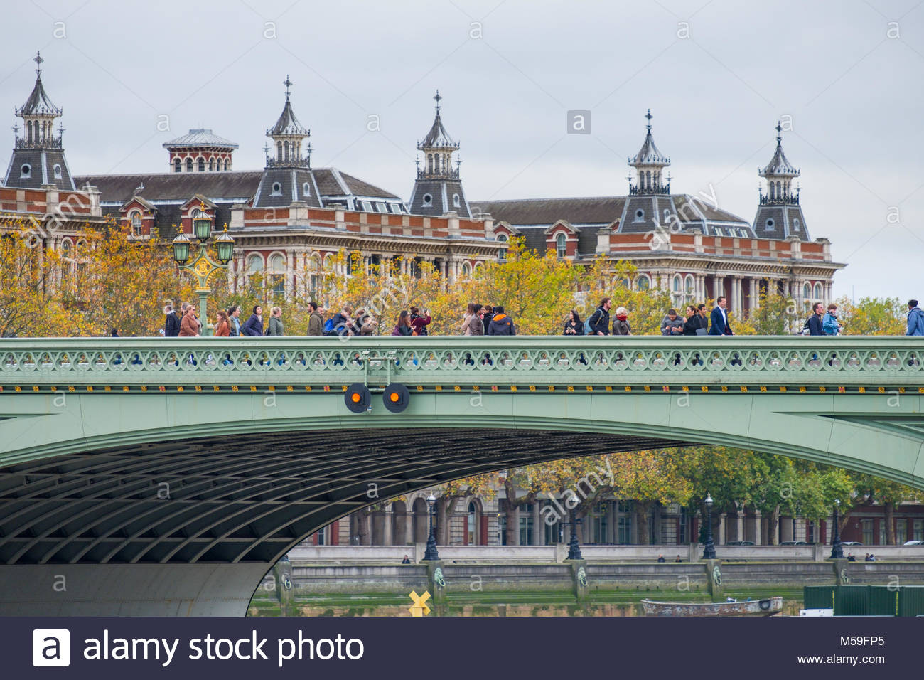 People walking on Westminster Bridge with Saint Thomas Hospital South Wing in the background, City of Westminster, - Stock Image