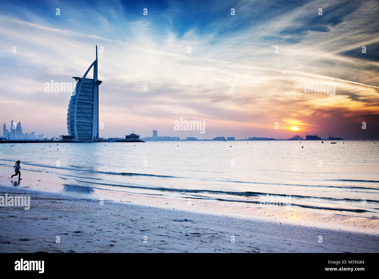 DUBAI, UAE - FEBRUARY 2018 :The world's first seven stars luxury hotel Burj Al Arab at sunset seen from Jumeirah - Stock Image