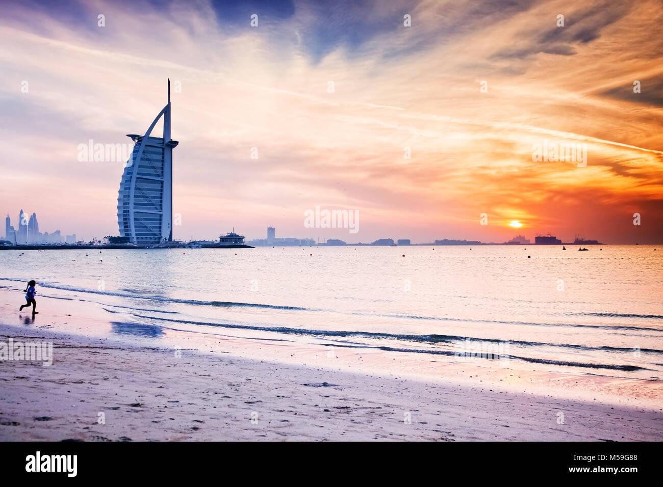 DUBAI, UAE - FEBRUARY 2018 :The world's first seven stars luxury hotel Burj Al Arab at sunset seen from Jumeirah - Stock Image