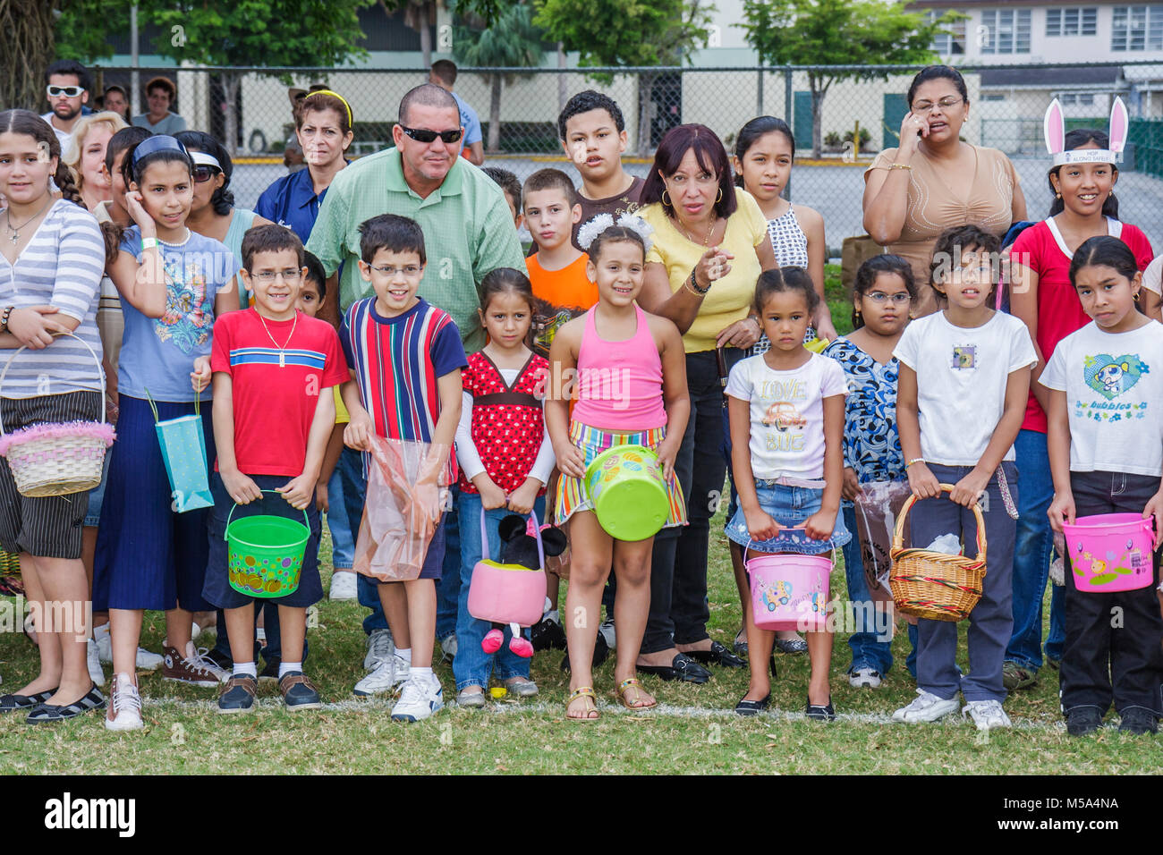 Hispanic festive tradition egg hunt boys girls outdoor starting line parent anticipate compete - Stock Image