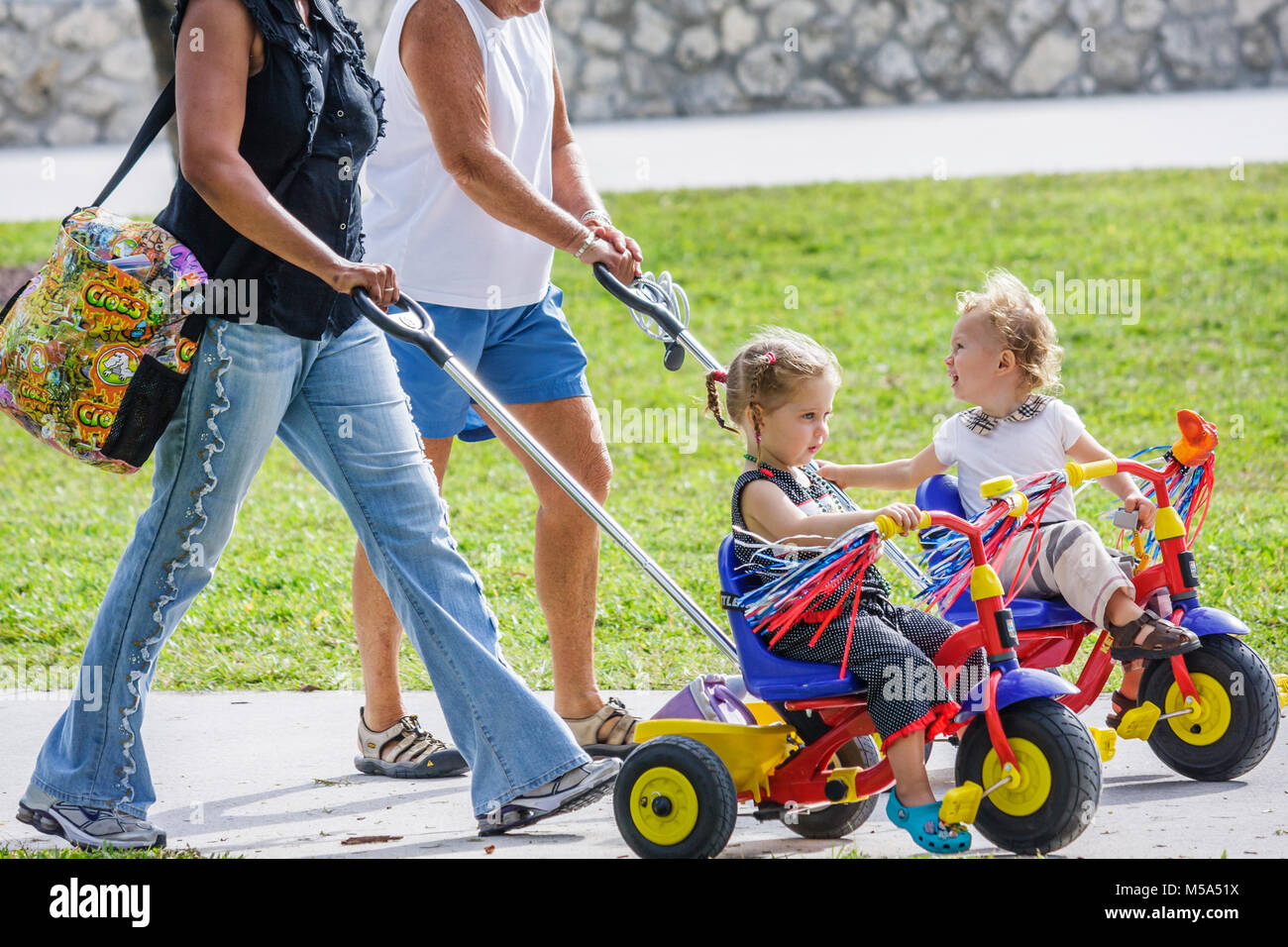 Lummus Park toddlers tricycles pushed Black nanny grandmother child care babysit outdoor - Stock Image