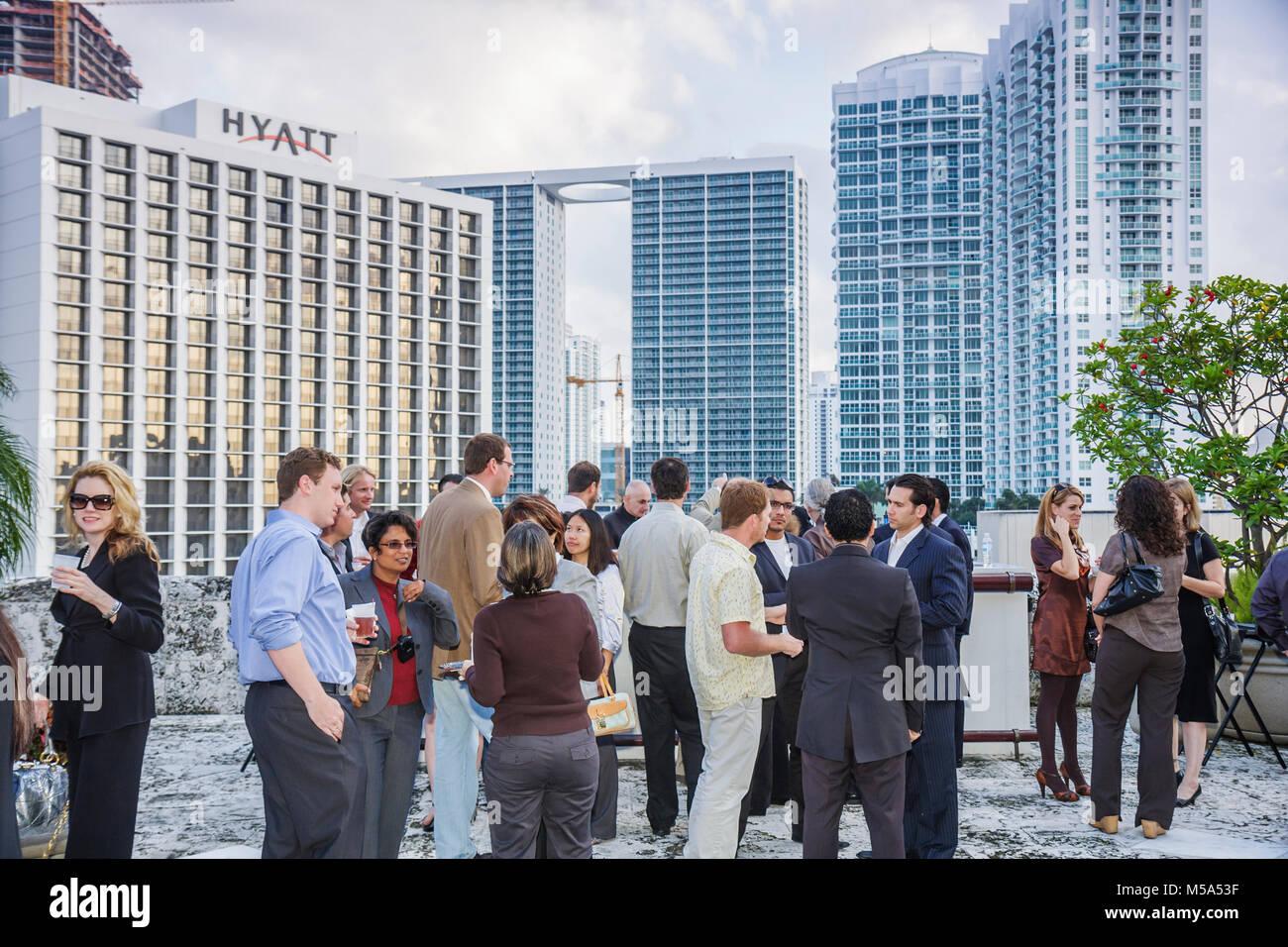 networking professional reception men women Hyatt Hotel high rise condominiums - Stock Image