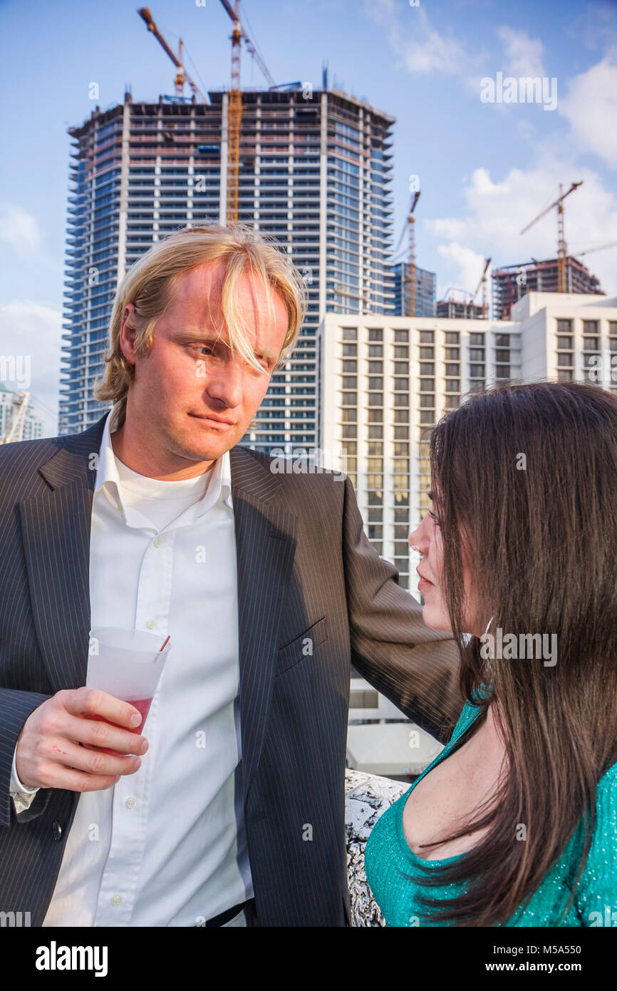 networking high rise construction condominium building reception outdoor man woman drinking seduce body language - Stock Image