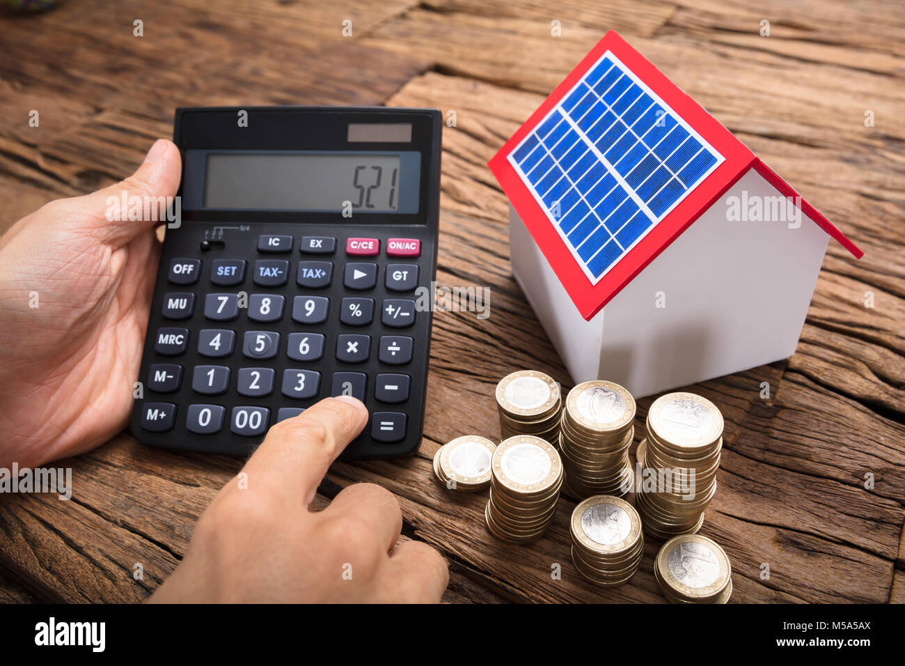 Businessman using calculator by coins and model home with