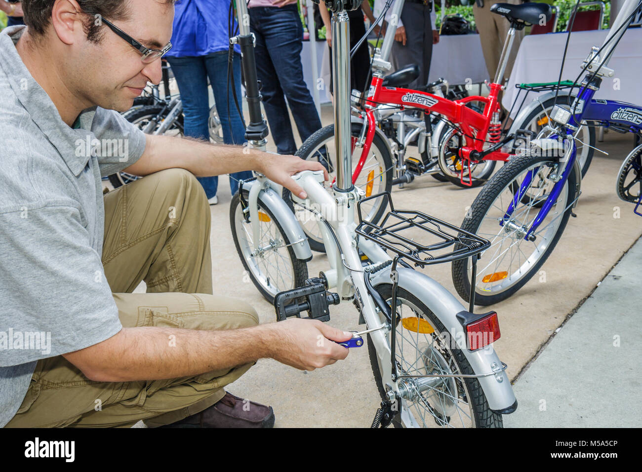 Bike to Work Week Citizen Bike folding repair man product demo tighten bicycle tool - Stock Image