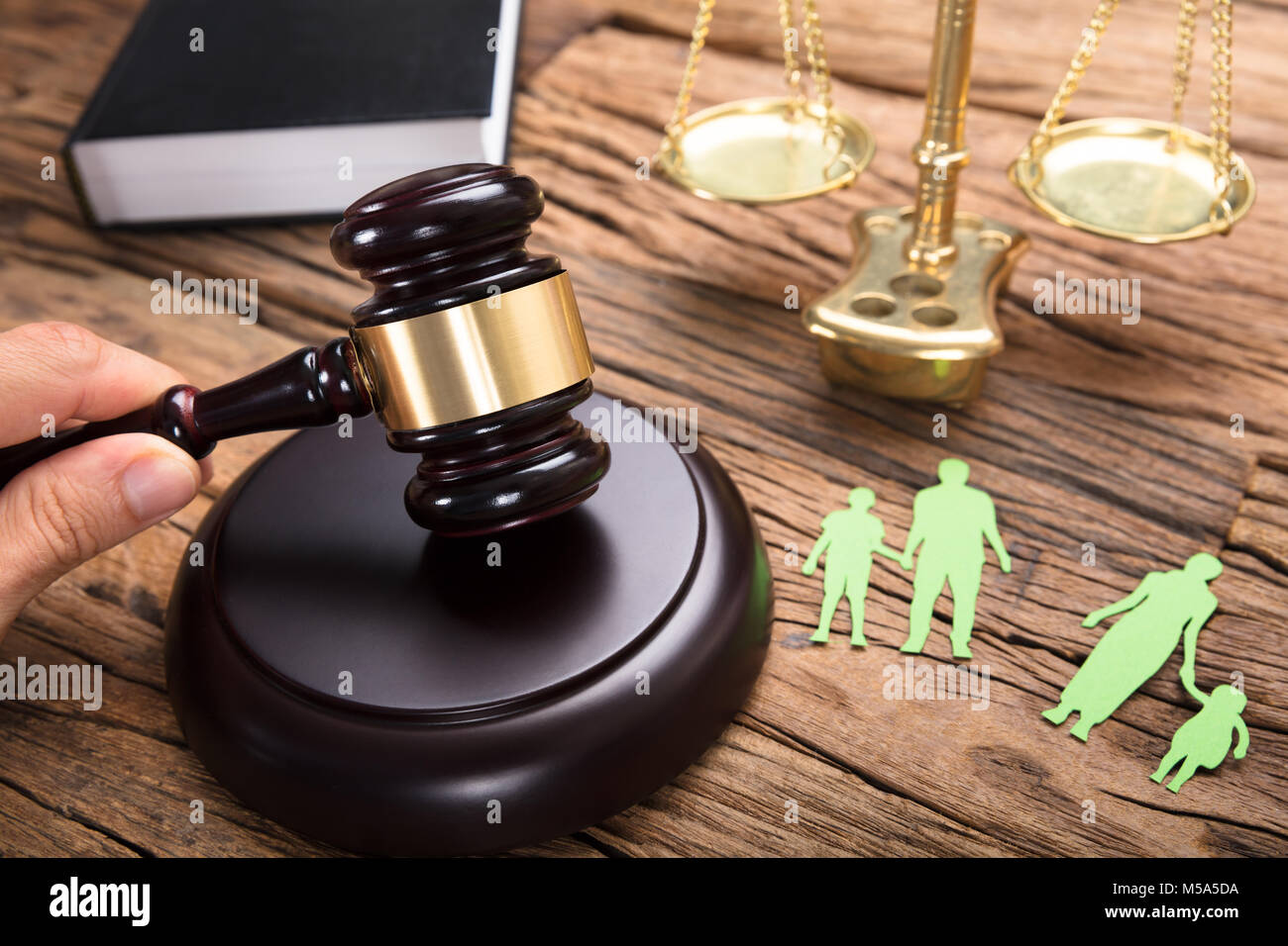 Judge hitting mallet by separated paper family and justice scale on wooden table - Stock Image