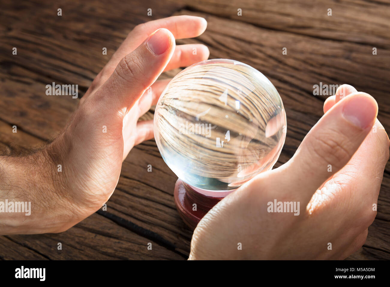 Businessman fortune telling and predicting future at wooden table - Stock Image
