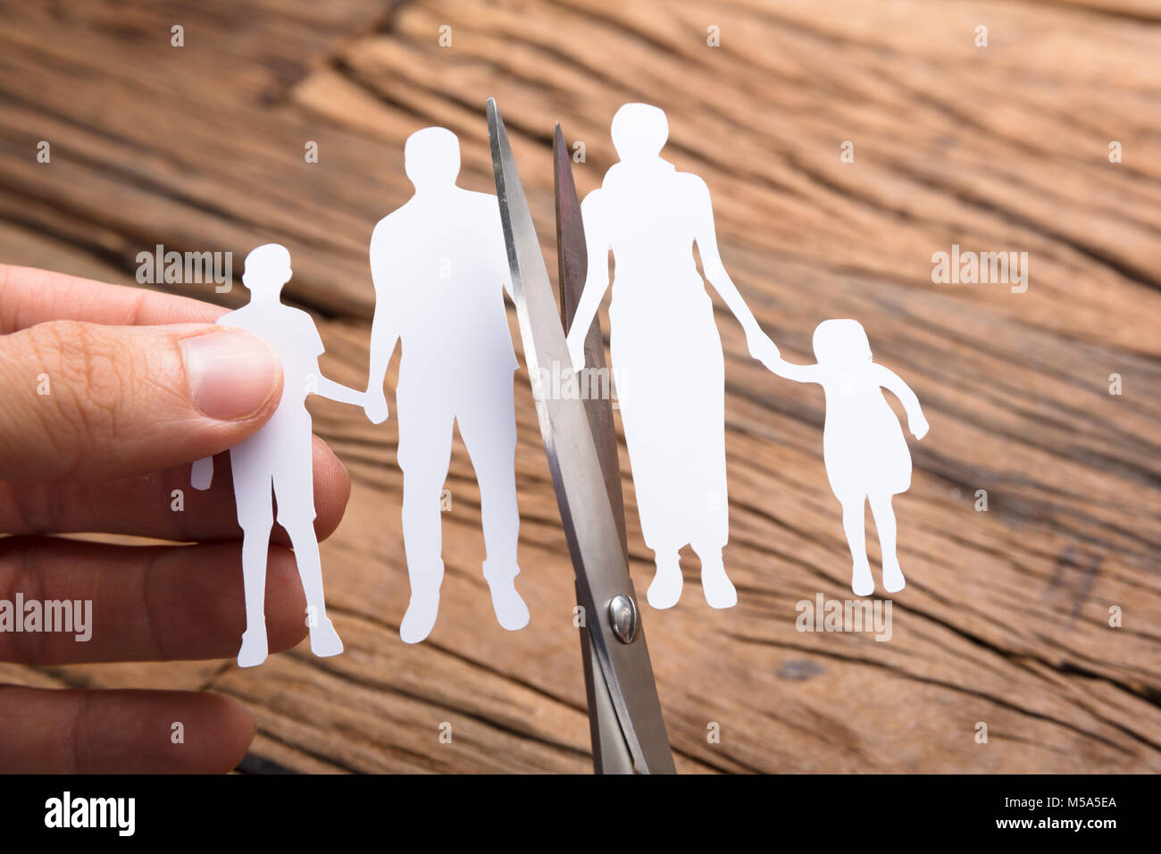 Cropped image of hand cutting paper family with scissors over wooden table - Stock Image