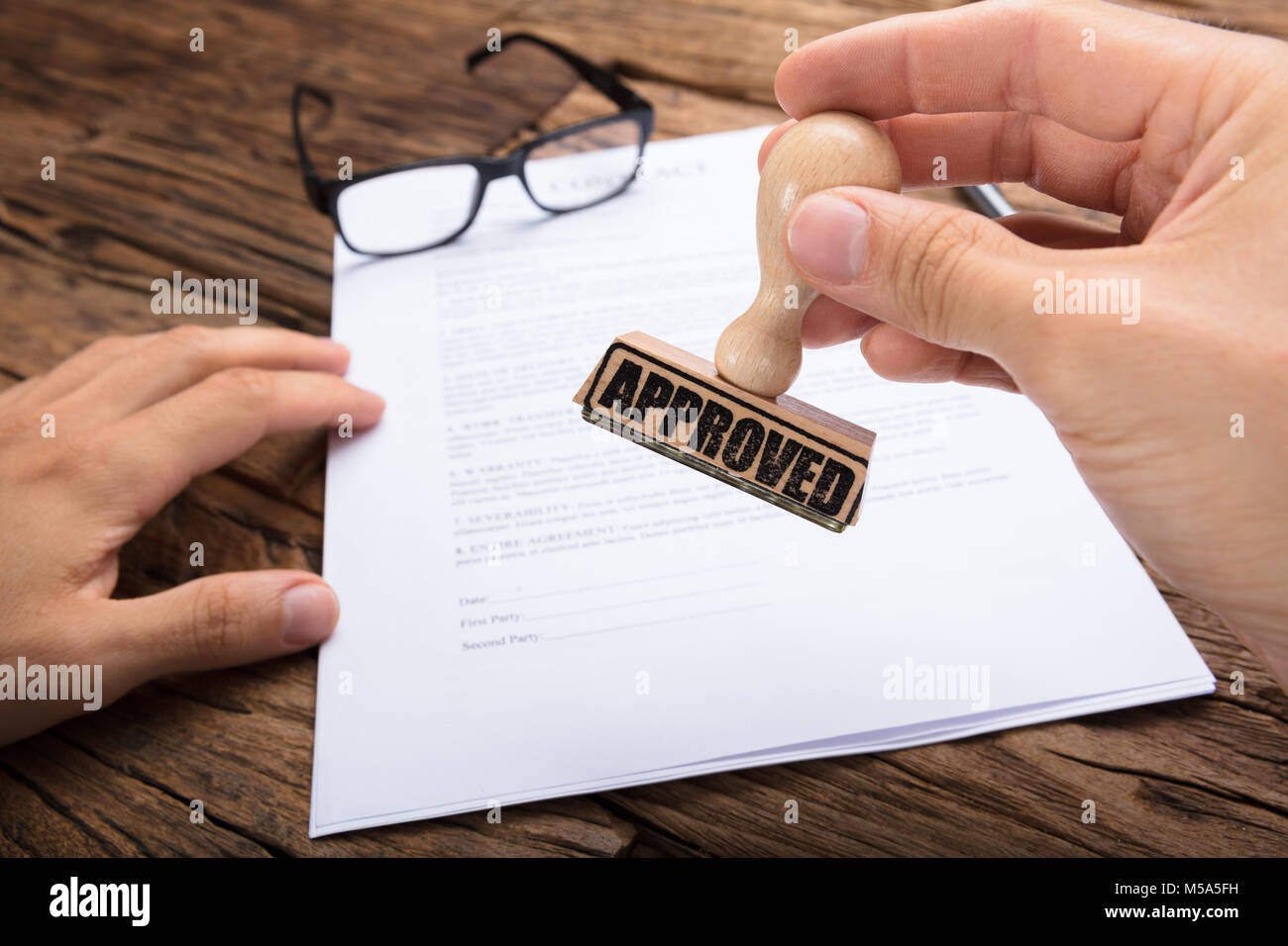 Cropped hands of businessman holding approved stamp over contract paper at wooden table Stock Photo