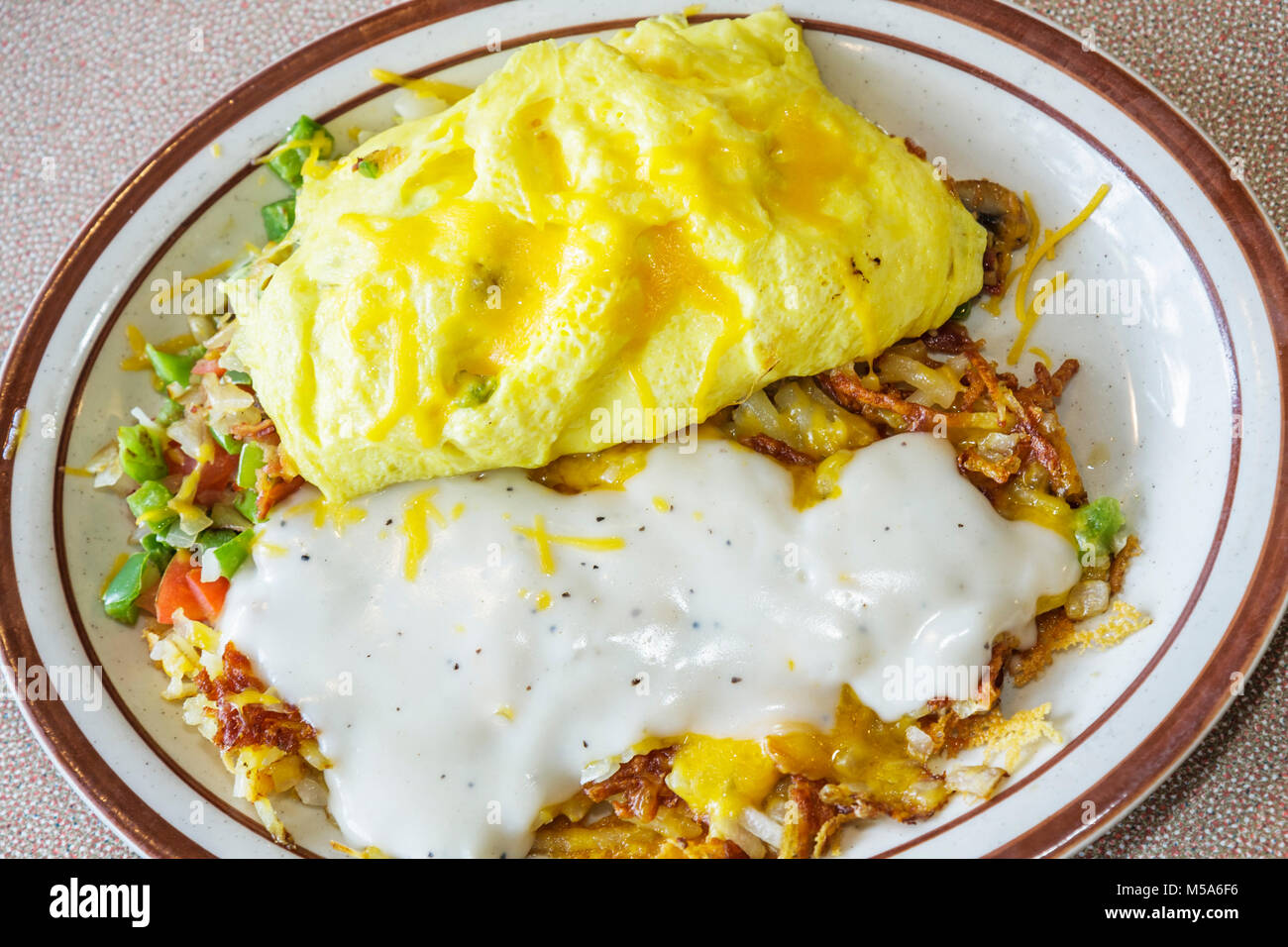 Hialeah Gardens Denny's Restaurant Ultimate Omelet hash browns food plate breakfast sauce - Stock Image