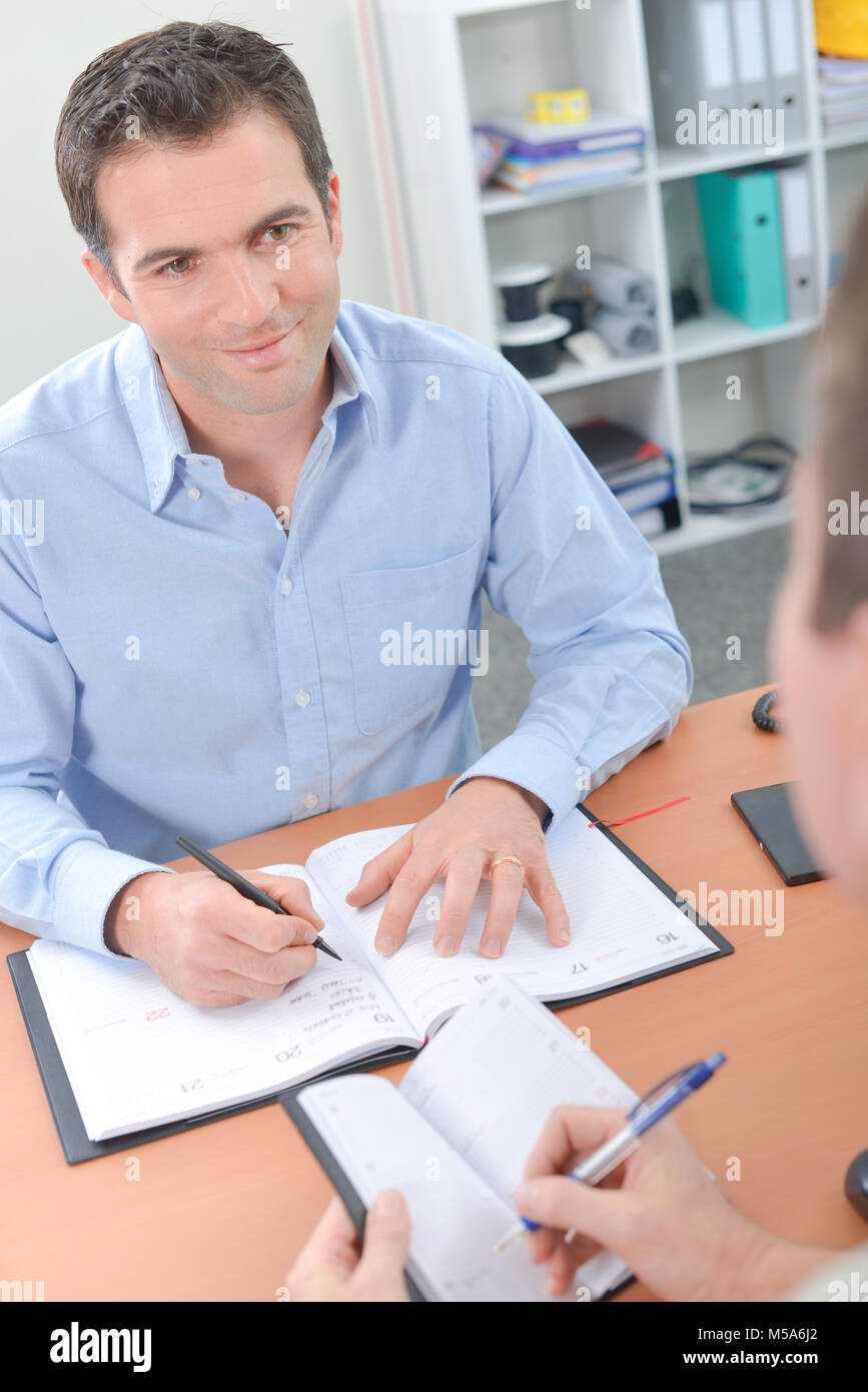 Two men noting dates in their diaries - Stock Image