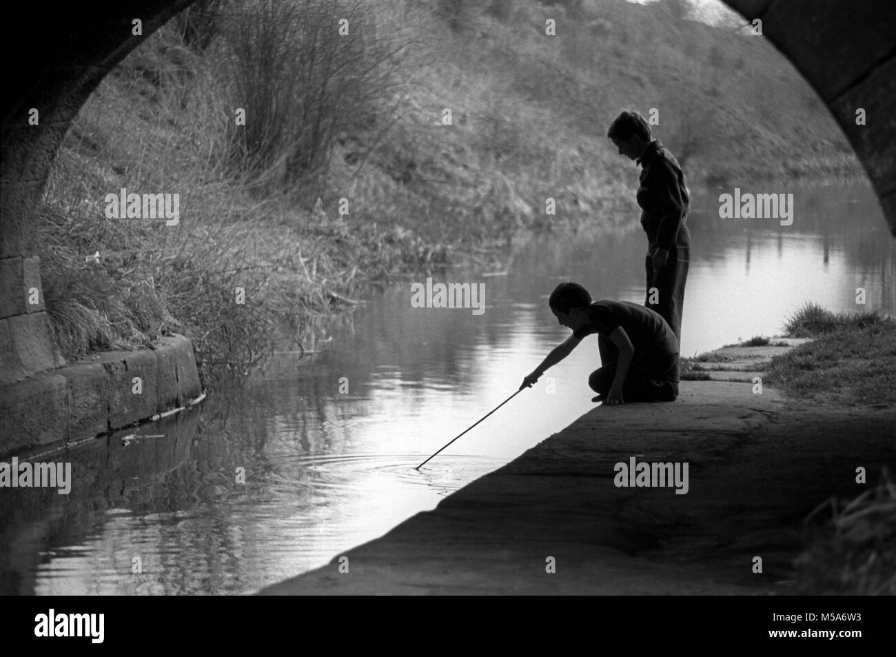 UK, England, Cheshire, Congleton, Buglawton, children playing with stick in Macclesfield Canal - Stock Image