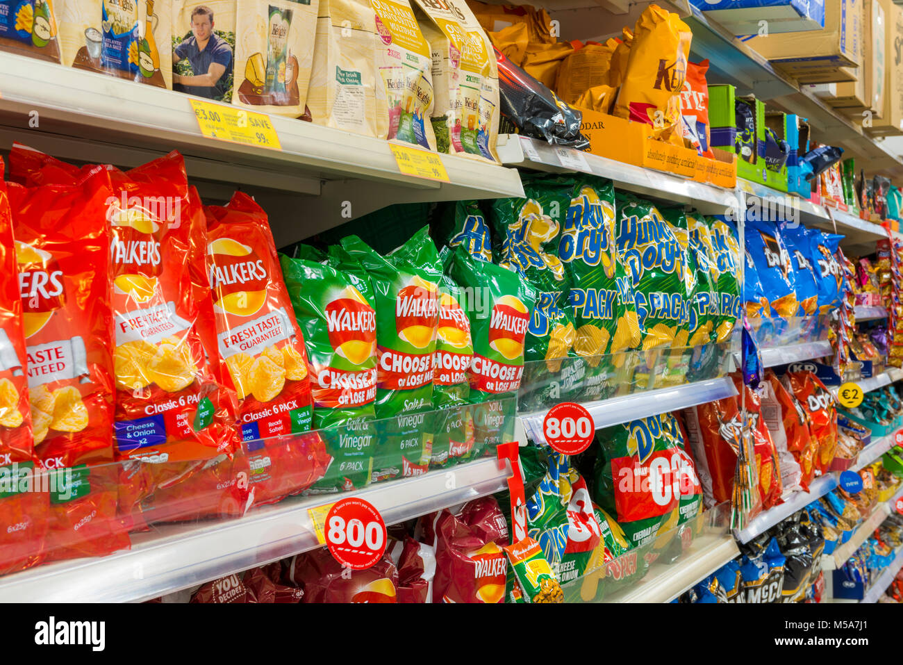 Crisps / potato chips on supermarket shelves - Stock Image