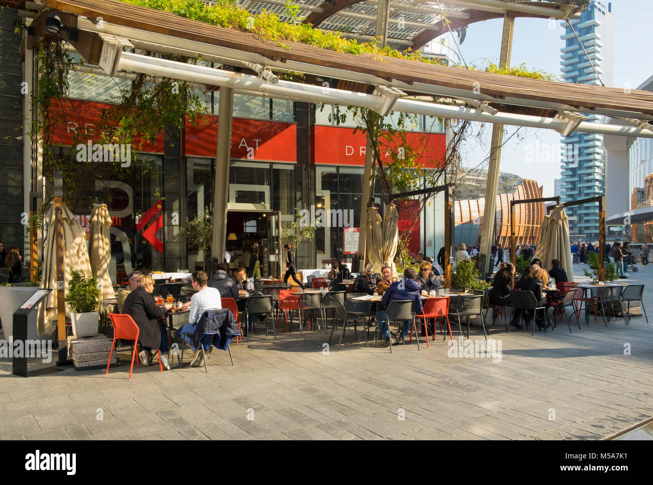 People at a street cafe in the Porta Nuova, Milan, Italy - the central business district - Stock Image