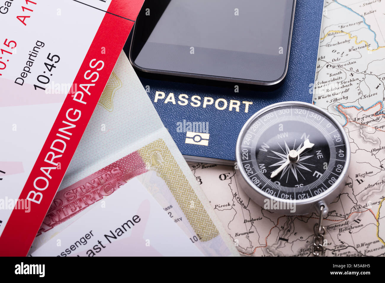 High Angle View Of Smartphone, Boarding Pass Ticket, Passport And Compass On Map - Stock Image
