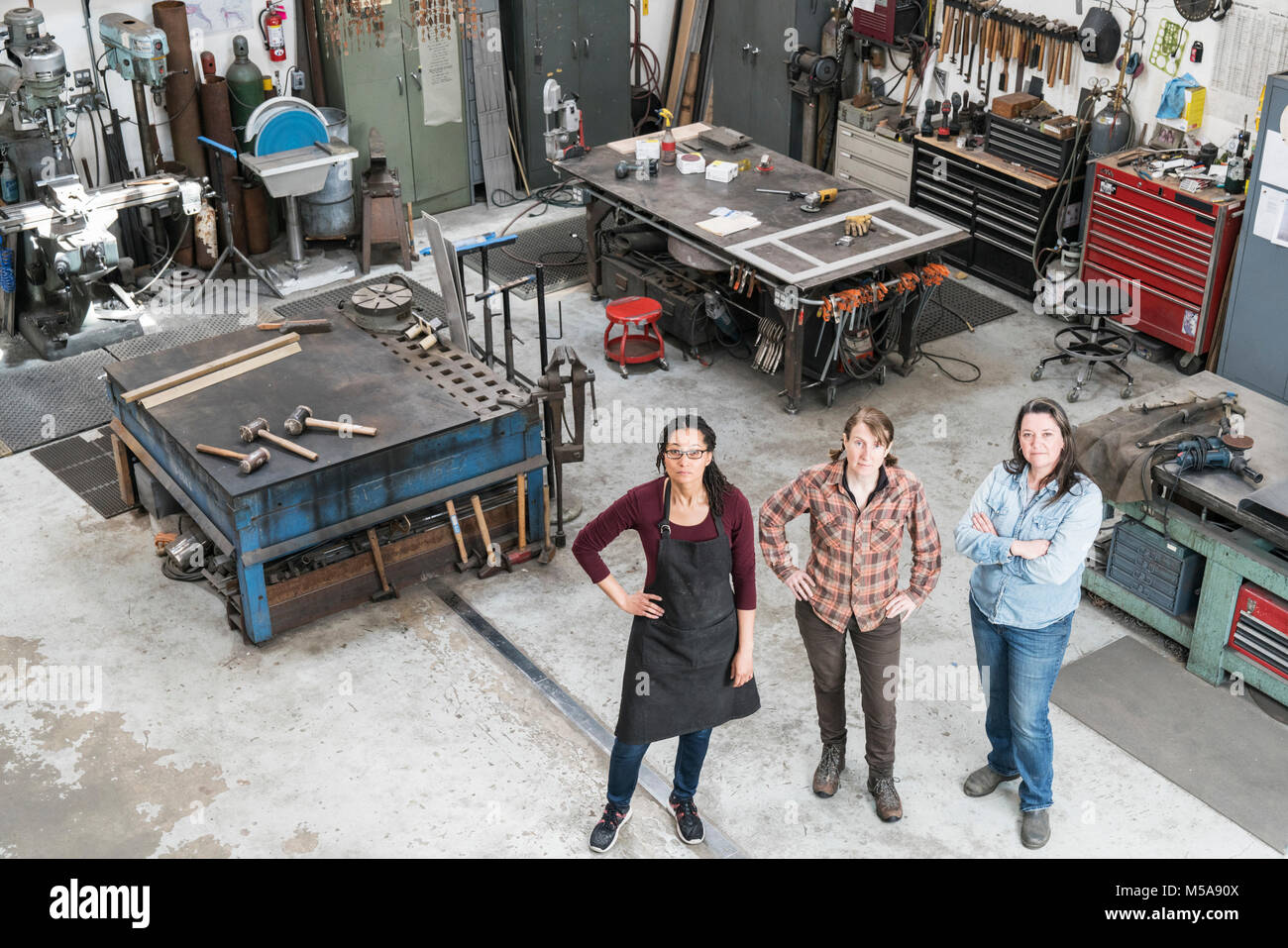 High angle view of three women standing in metal workshop, looking at camera. - Stock Image