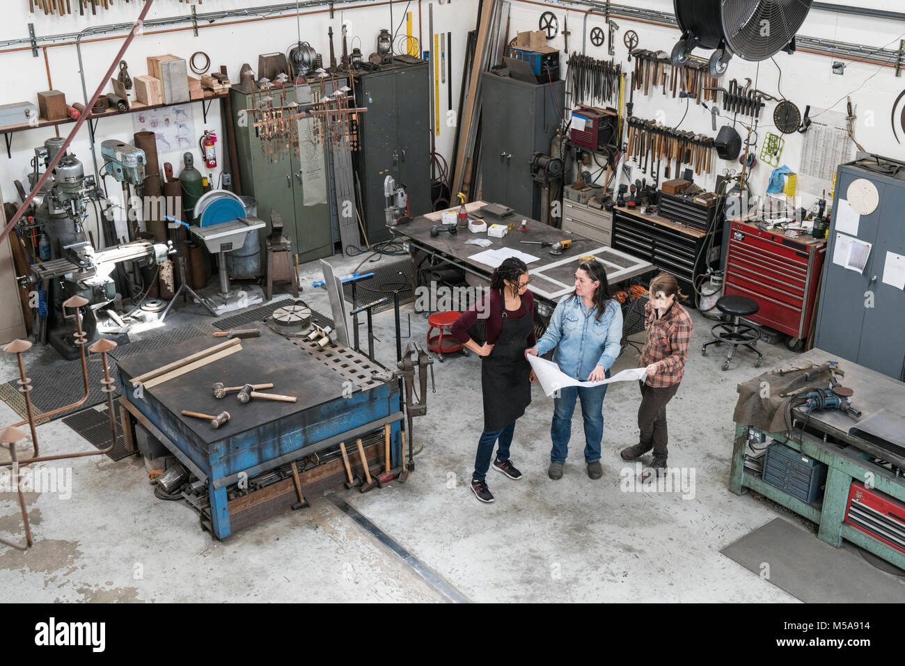 High angle view of three women standing in metal workshop, holding technical blueprint. - Stock Image