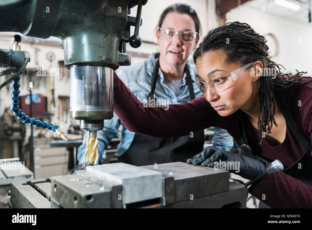 Two women wearing safety glasses standing in a metal workshop, working on metal drilling machine. Stock Photo