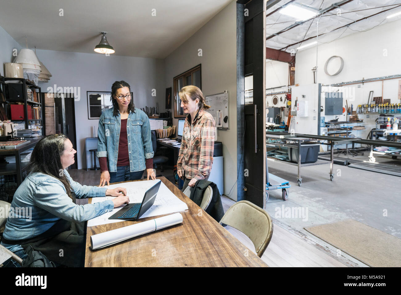 Three women gathered around table in office area of a metal workshop. Stock Photo