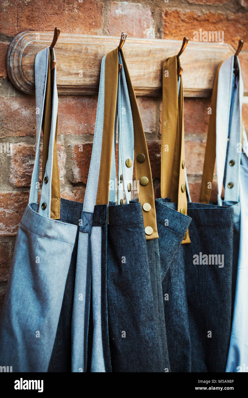 Denim work aprons hanging on a row of hooks on a brick wall Stock