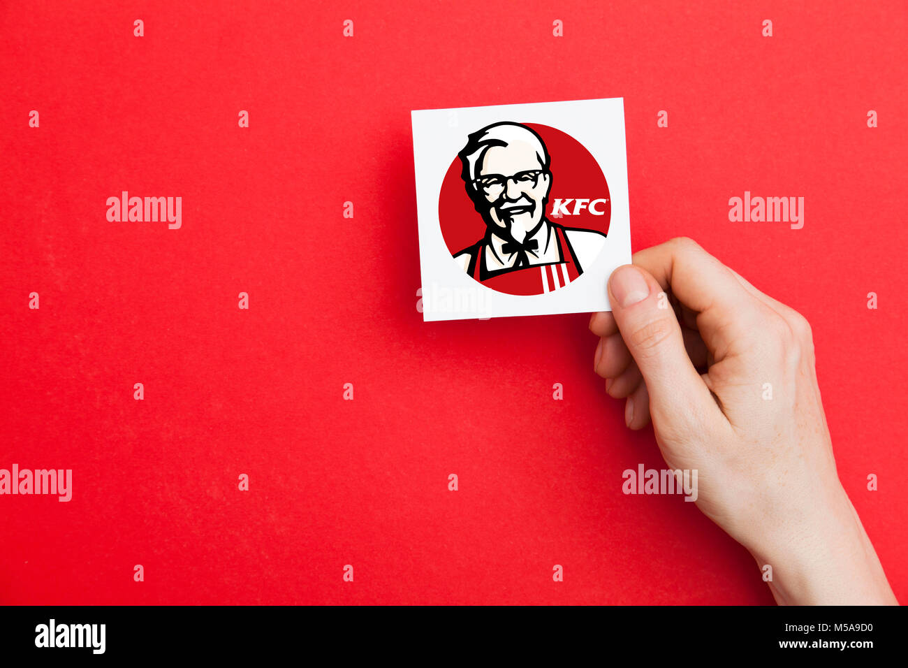 LONDON, UK - February 21st 2018: Hand holidng aKFC fast food sign. KFC is an american fast food company that specializes - Stock Image