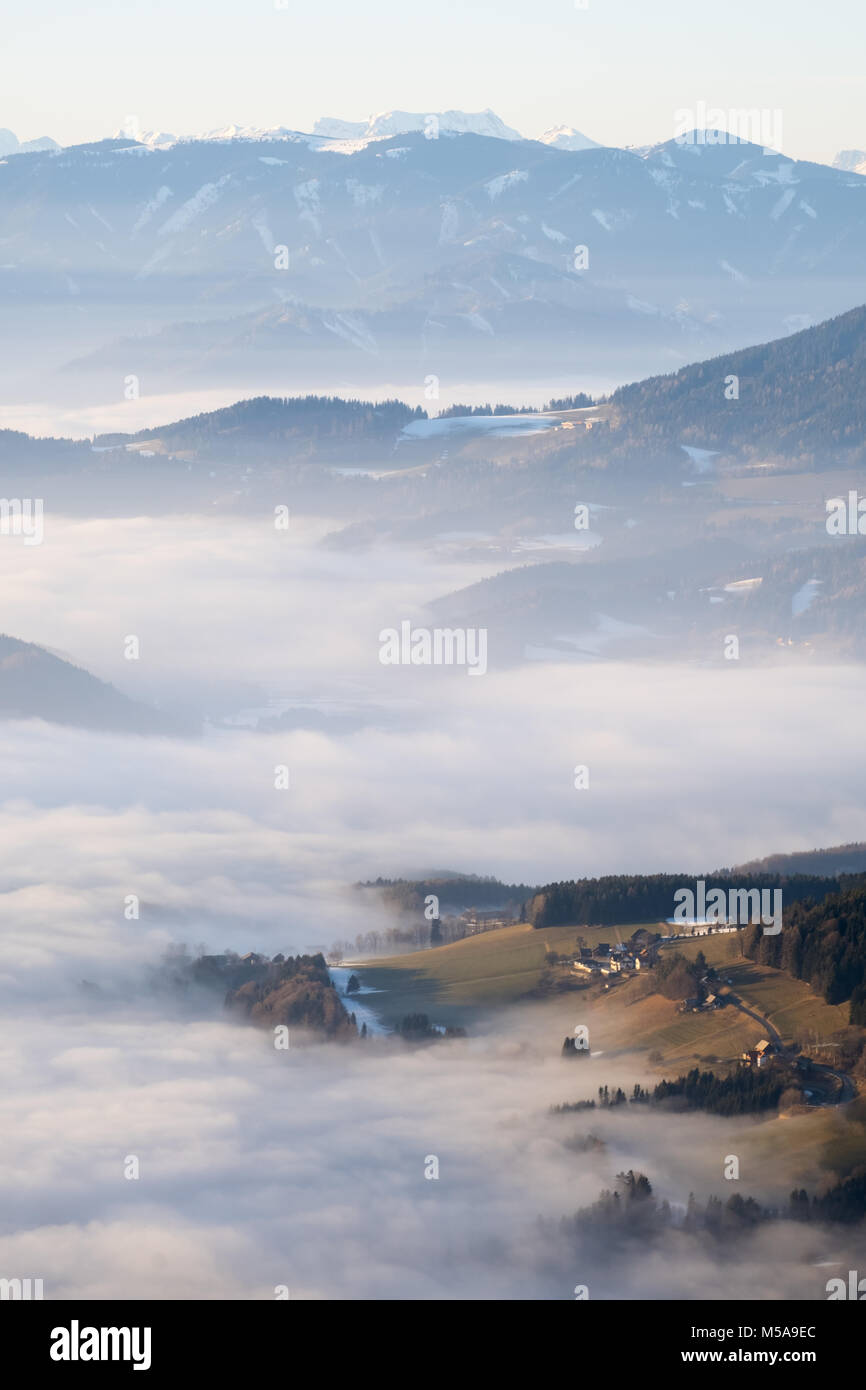 Hill looking through low stratus fog with mountain range Hochschwab in the background Stock Photo
