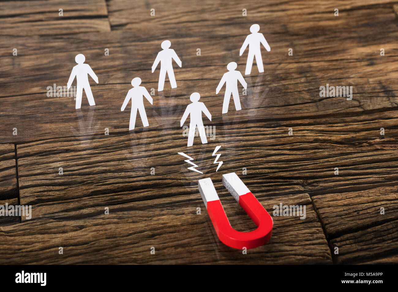 Close-up Of A Red Horseshoe Magnet Attracting Paper Cut Out On Desk - Stock Image