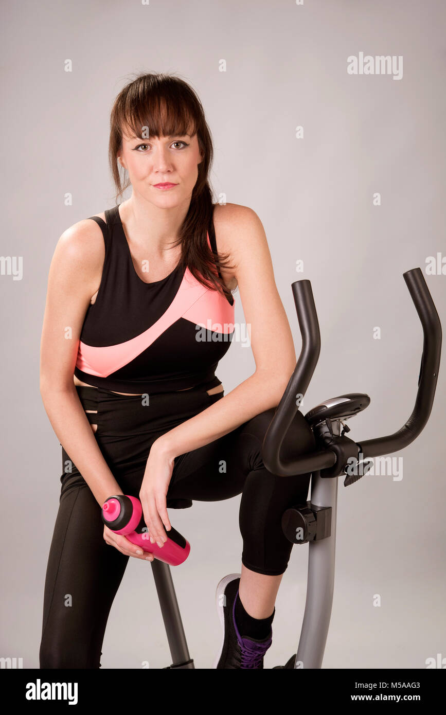 Woman on an exercise bike holding a plastic water bottle - Stock Image