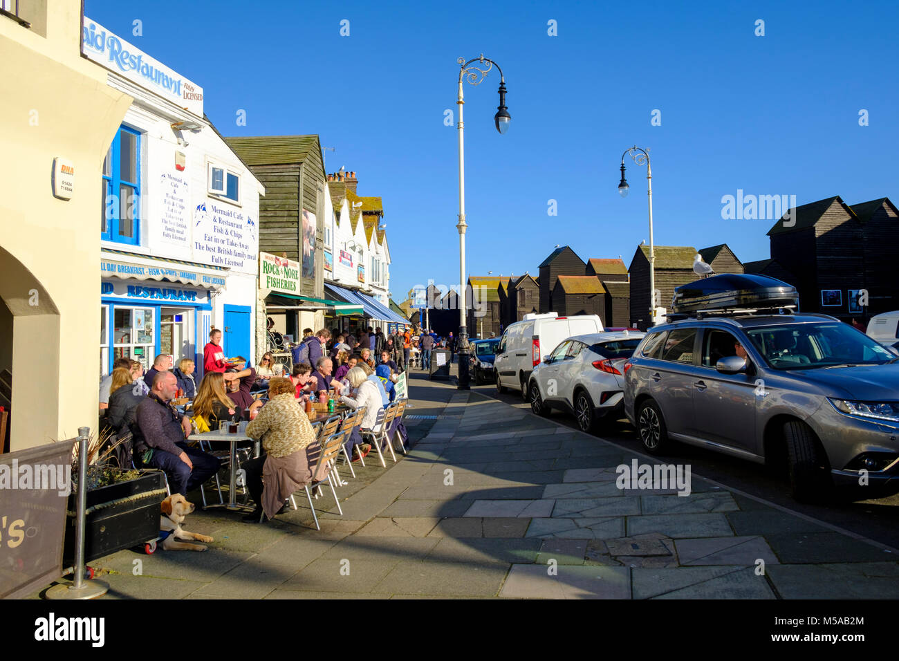 Hastings, people eating outside on a sunny warm February day at Rock-a-Nore, by the net huts on the seafront, East - Stock Image