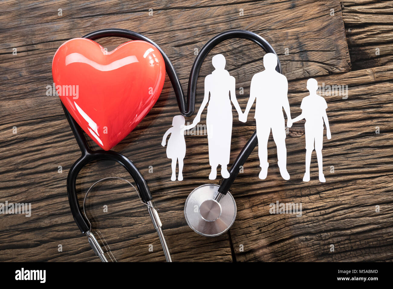Elevated View Of Family Cut Out And Red Heart With Stethoscope On Desk - Stock Image