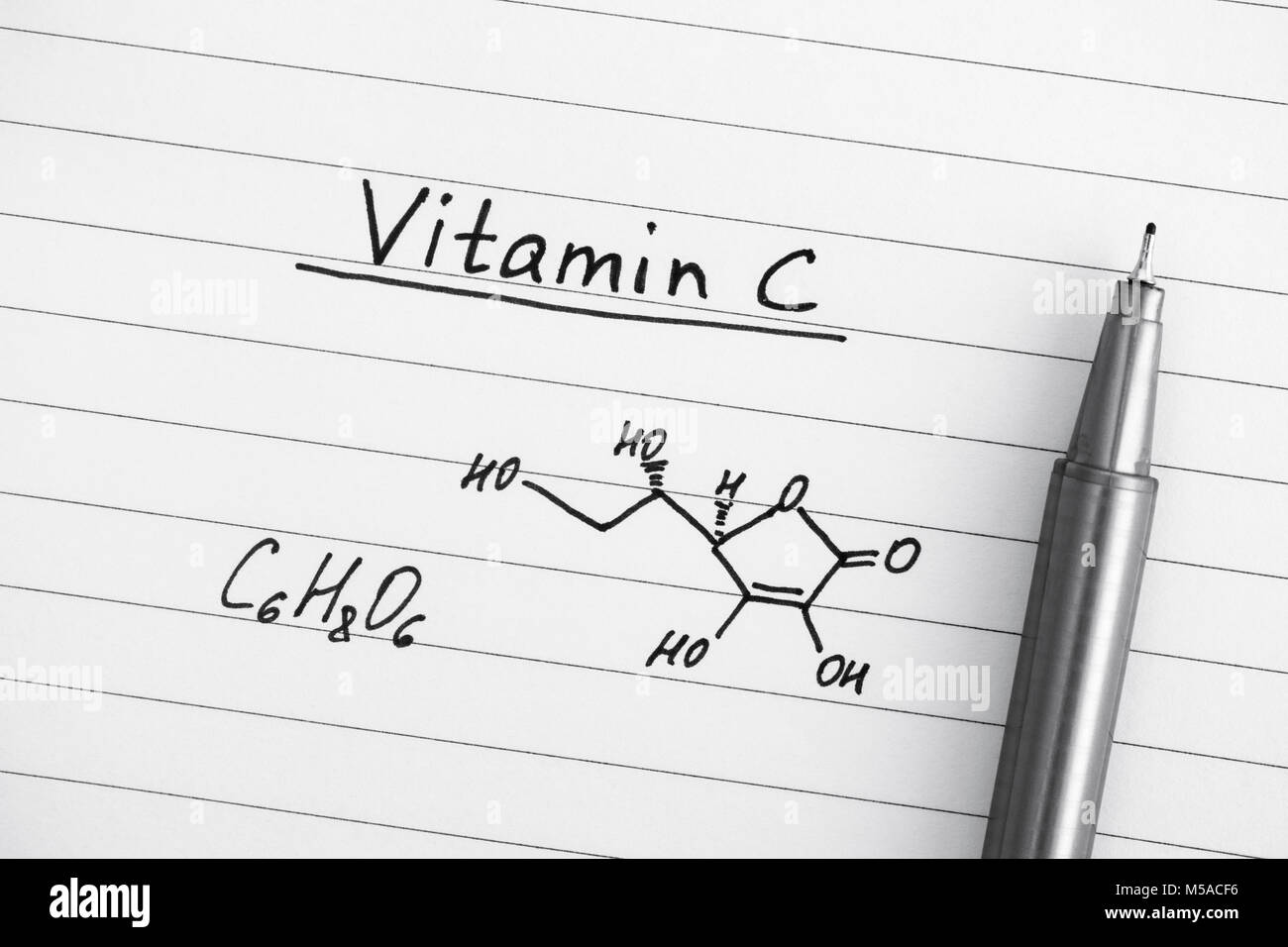 Chemical formula of Vitamin C with pen. Close-up. - Stock Image