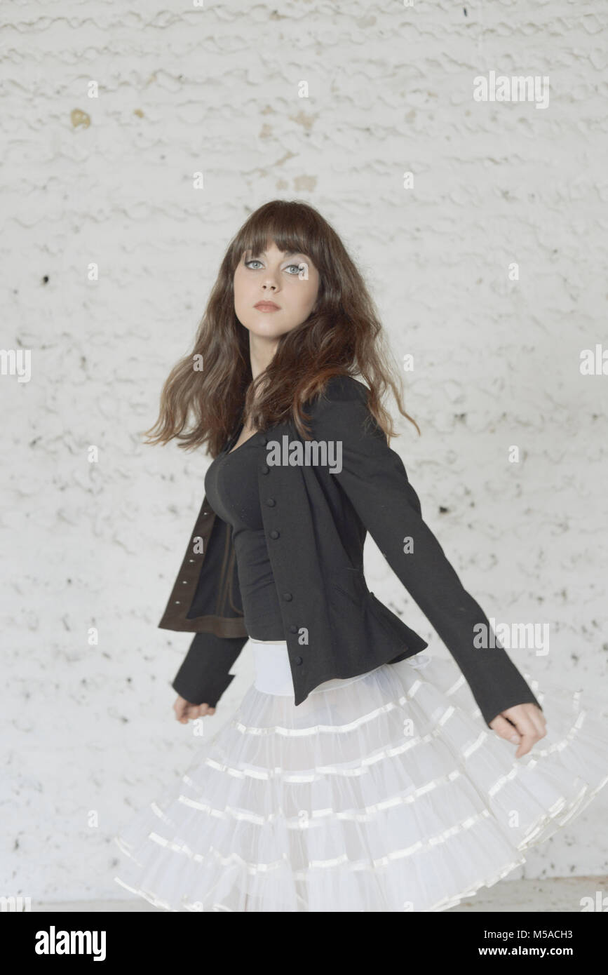 A beautiful girl with long brown hair dances in front of a white painted wall- her hair moves, she is unsmiling - Stock Image