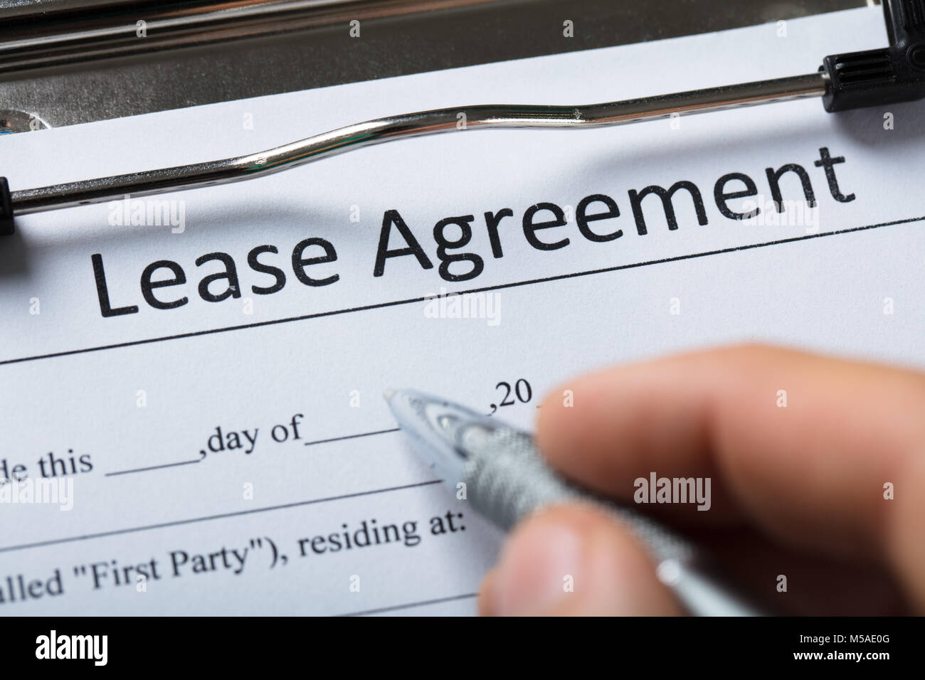 Close Up Of A Human Hand Filling Lease Agreement Form With
