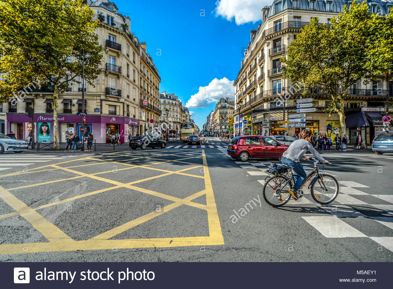 A bicyclist rides through an intersection along the Rue du Rivoli with cars and shops on a sunny summer day in Paris - Stock Image
