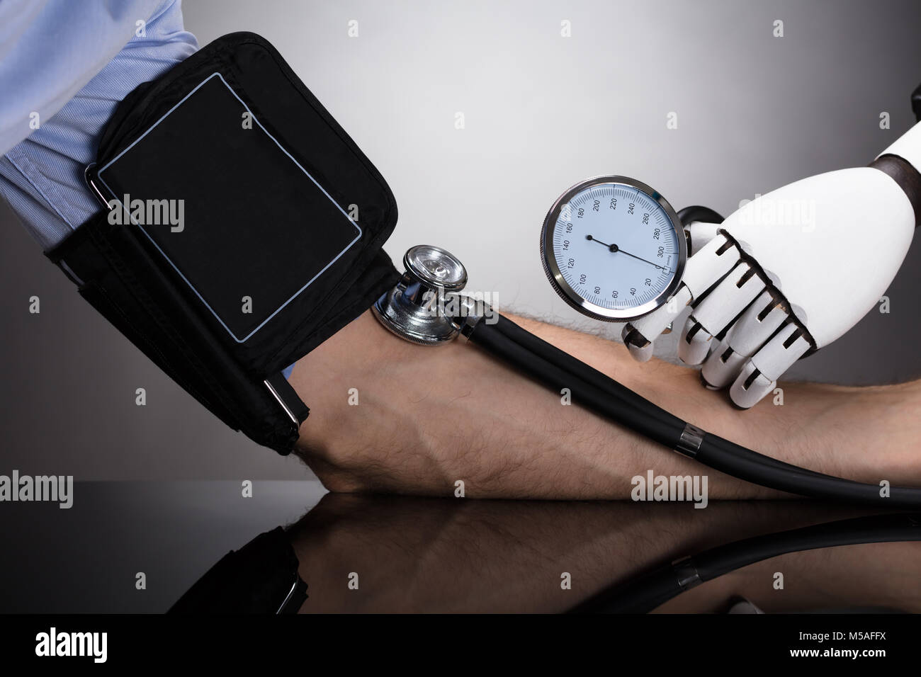 Robot's Hand Checking Person's Blood Pressure On Grey Background - Stock Image