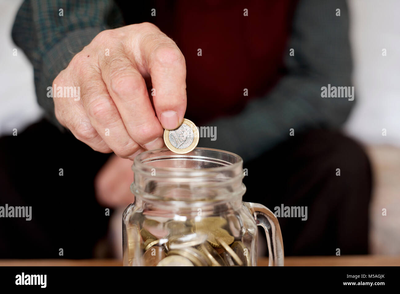 closeup of an old caucasian man saving a one euro coin in a glass pot - Stock Image