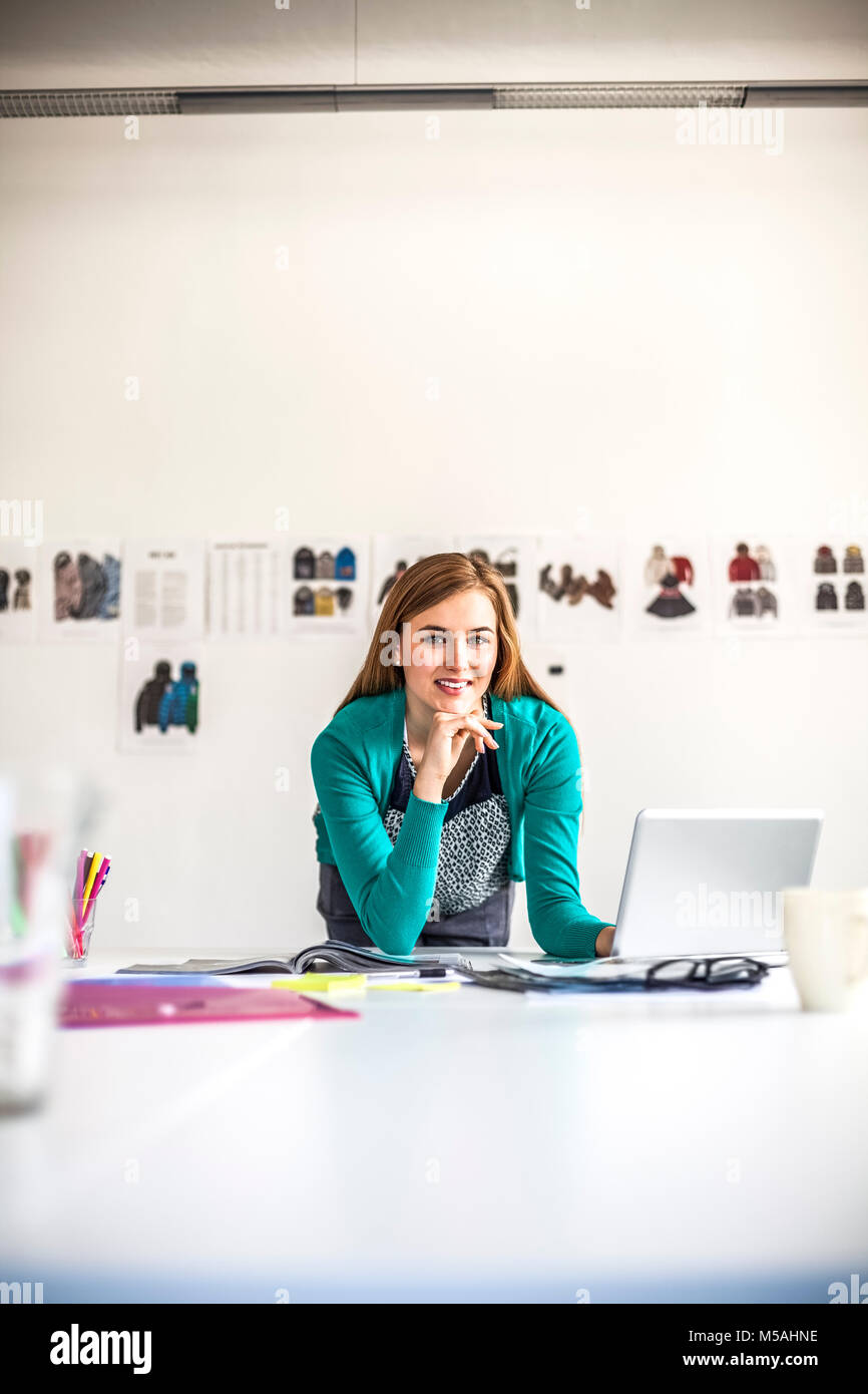 Portrait of confident young female fashion designer with laptop in creative office - Stock Image