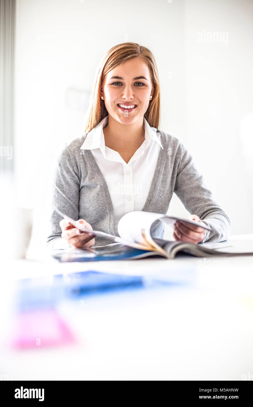 Portrait of young businesswoman reading brochure at table in office - Stock Image