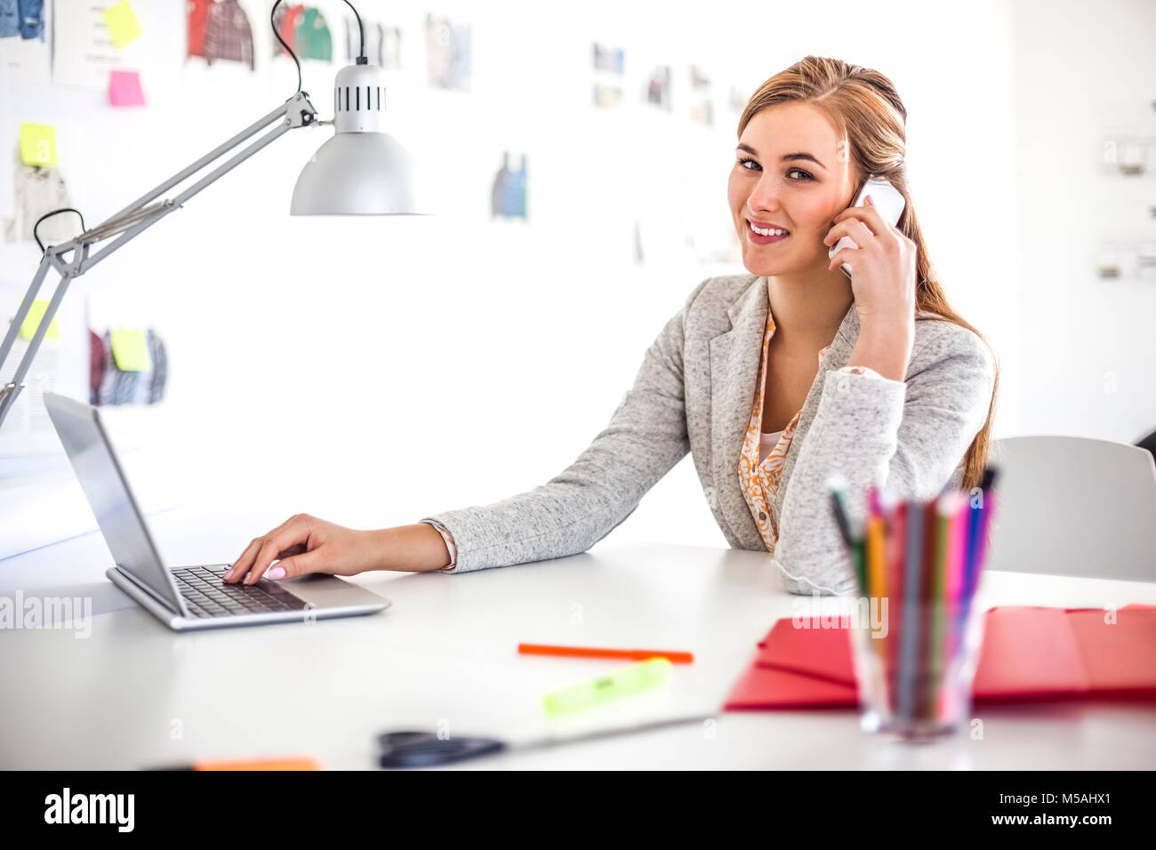 Portrait of young businesswoman using cell phone and laptop in office - Stock Image