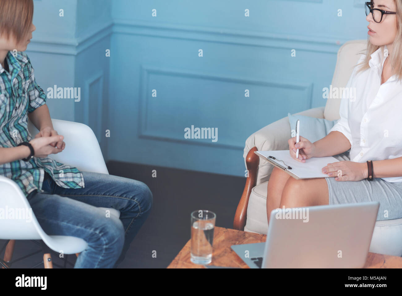 Professional psychotherapist discusses anxiety and worries with teen boy Stock Photo