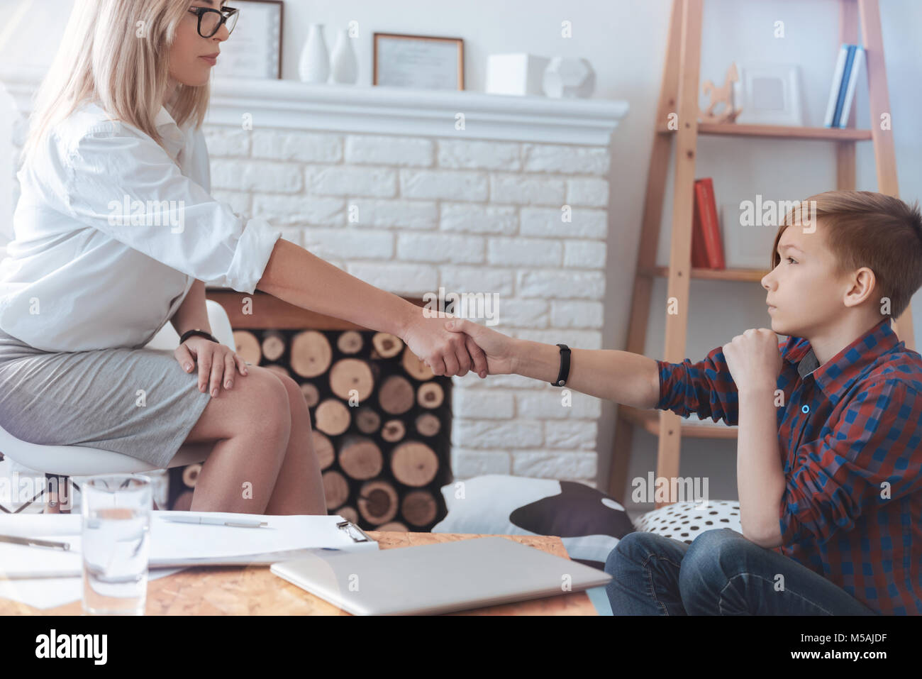 Professional psychotherapist and teenage boy shaking hands in office Stock Photo