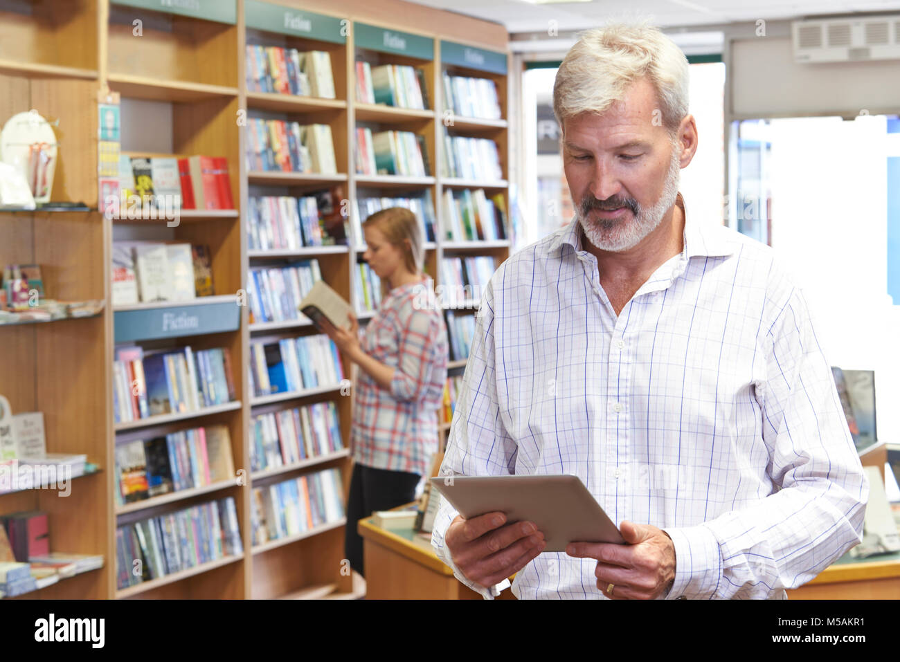Male Bookstore Owner Using Digital Tablet With Customer In Background - Stock Image