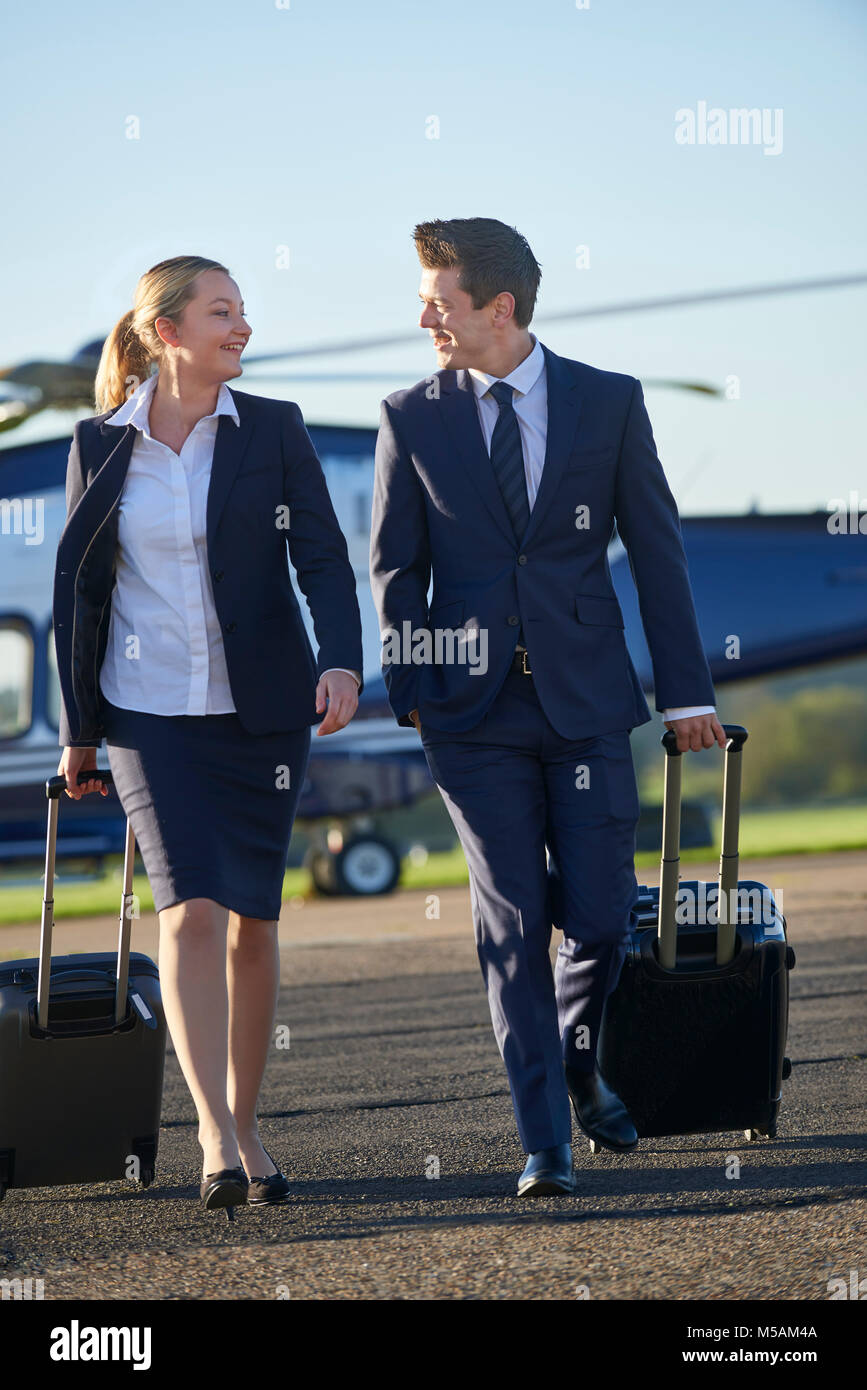 Businesswoman And Businessman In Discussion As They Walk Away From Helicopter - Stock Image