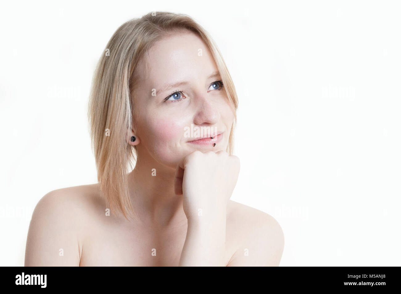 blue-eyed blonde young woman looking at copy space - Stock Image