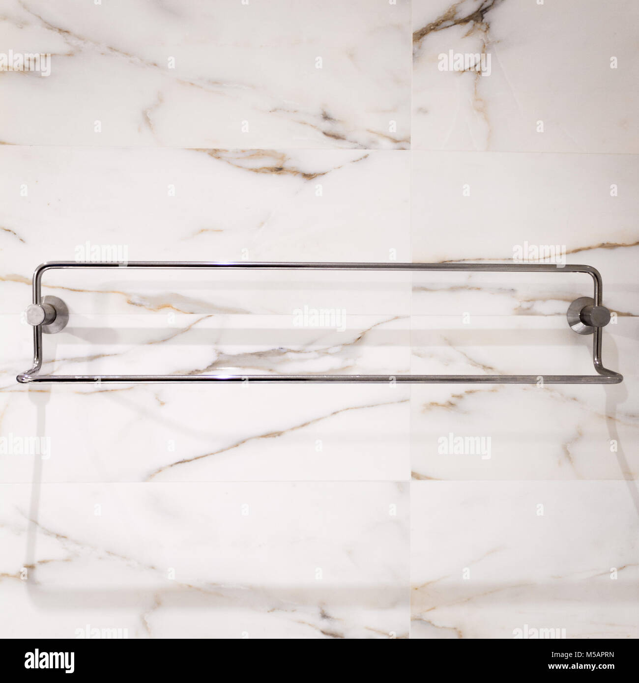 A bathroom towel rack in steel, on a white marble tile wall Stock ...