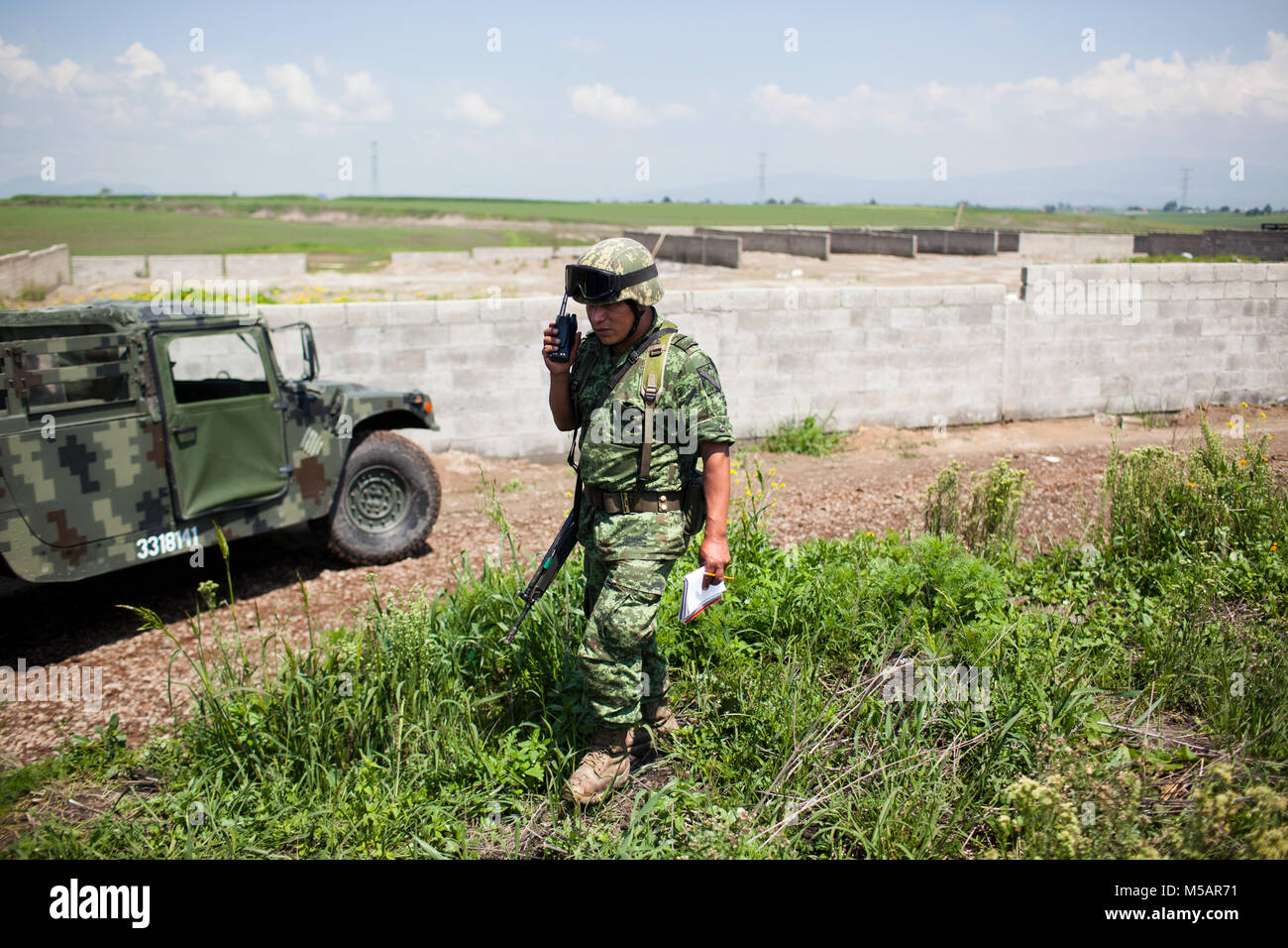 A Mexican Army soldier guards a small farm house that was used by Joaquin 'El Chapo' Guzman to escape Altiplano - Stock Image