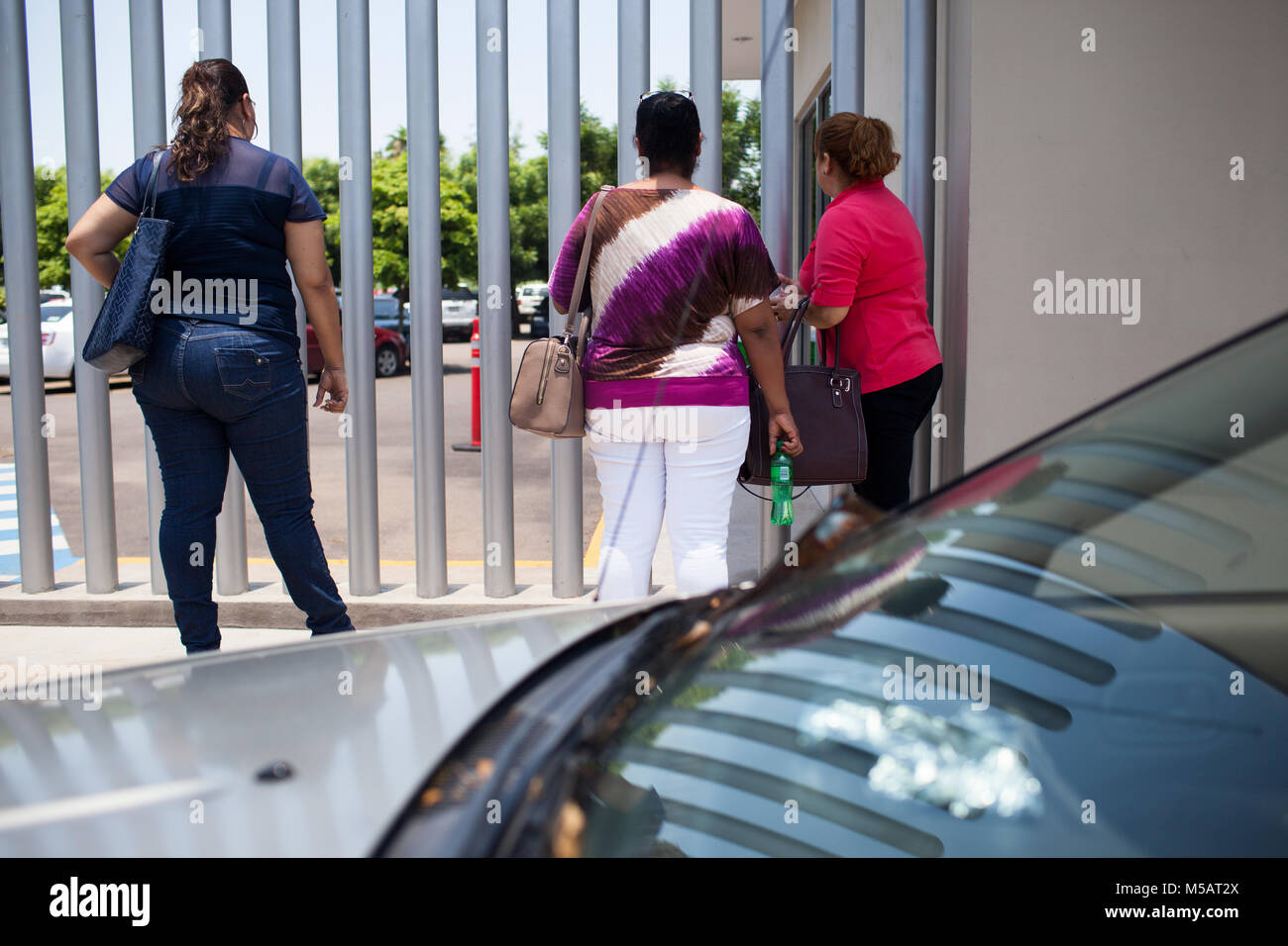 Widowers of police officers who were killed talk through the gate outside the Sinaloa State congress in Culiac‡n, - Stock Image